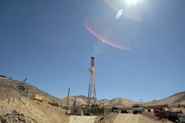An oil rig is raised for the first time to drill an escape hole for trapped miners in Copiapo