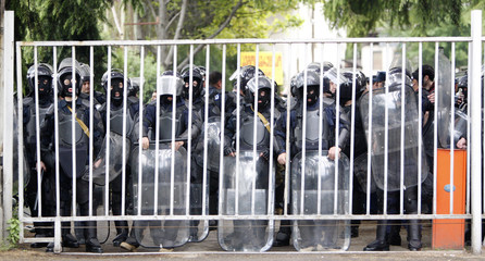 Riot police stand guard in the courtyard of a Television broadcast station during an opposition rally in Tbilisi