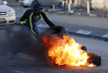 Palestinians clash with  Israeli border police during clashes at a checkpoint between Shuafat refugee camp and Jerusalem