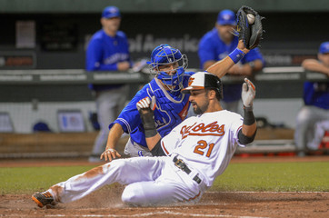 Toronto Blue Jays Arencibia has the ball but is late with the tag as Baltimore Orioles Markakis scores on a sacrifice fly off the bat of teammate Wieters during their MLB American League baseball game in Baltimore