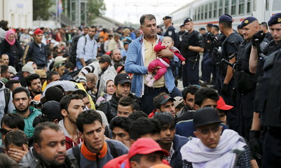 A migrant holds a baby beside police at the train station in Tovarnik