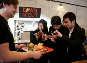 Customers take pictures of Pokeburgs, hamburgers in the form of Pokemon characters, at Down N' Out Burger restaurant in Sydney, Australia