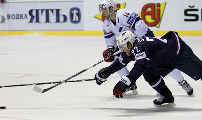 Stephane da Costa of France challenges Yan Stastny of US during their qualification round Group F game at the Ice Hockey World Championships in Kosice