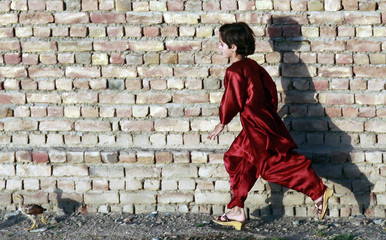 A young Afghan girl runs after a chicken in a residential neighborhood close to CNS in Kandahar City