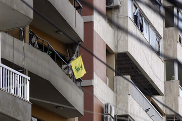 Woman stands on a balcony as a Hezbollah flag is seen on a balcony of a damaged building at the site of an explosion that occurred yesterday in Beirut's southern suburbs