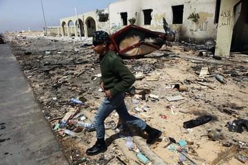 Rebel fighter walks amid debris in eastern Libya