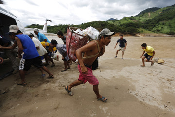 Residents carry food rations delivered by personnel of the Attorney General Office in the village of Omitlan