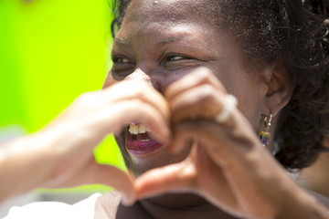 Voncille Greene, of College Park, Maryland, makes a heart symbol with a fellow mourner's hand during a funeral service for shooting victim Cynthia Hurd at Emanuel AME Church in Charleston
