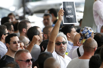 """A French taxi driver holds a leaflet which reads """"Uber go home"""" as striking taxi drivers gather near the Paris ring road during a national protest against car-sharing service Uber, in Paris"""