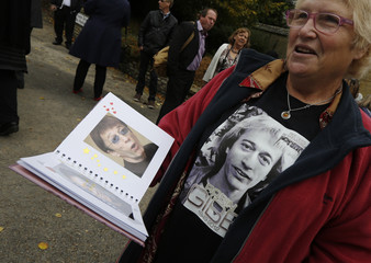 A woman holds an album of photographs at the unveiling of a blue plaque to honour Robin Gibb at his home in Thame, southern England
