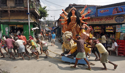 Labourers pull an idol of Durga, the Hindu goddess of power, through a street to be transported on a boat to a pandal or a temporary platform in Kolkata