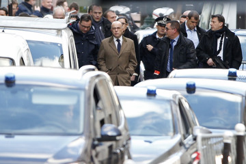French Interior Minister Bernard Cazeneuve leaves after a visit to the police station where a man was shot dead in the 18th district in Paris