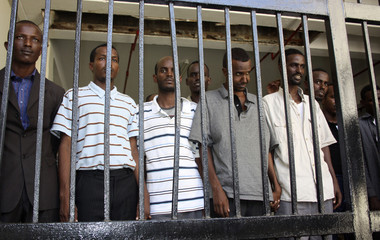 Freed Somali men, who had been charged with piracy earlier, wait for transport from the police cells at a court in Mombasa