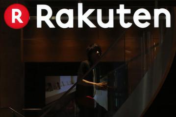 A staff of Rakuten Cafe is seen under a logo of Rakuten Inc in Tokyo