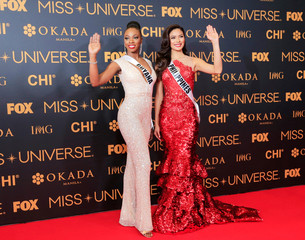 Miss Universe candidates Guyana Soyini Fraser of Guyana and Maxine Medinage of Philippines gesture for a picture during a red carpet inside a SMX convention in metro Manila