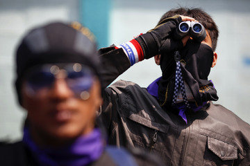 A guard uses binoculars to scan the area as anti-government protesters arrive to the Science and Technology ministry compound in Bangkok
