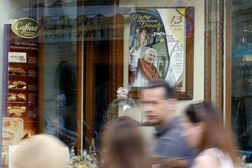 People walk past a picture of Pope Benedict XVI shown at an ice-cream shop in downtown Arezzo