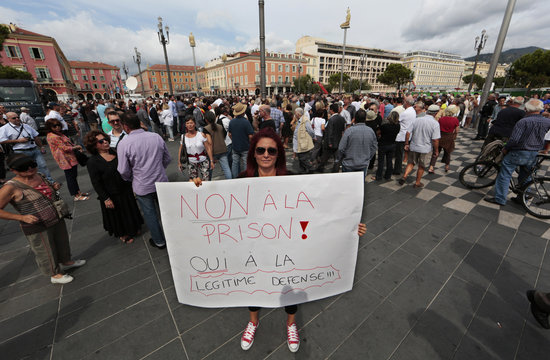 """A woman holds a poster which reads """"No to jail, Yes to legitimate self-defence"""" while people demonstrate in the centre of Nice to support jeweller Stephan Turk in Nice"""