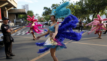 Traffic enforcers watch Filipino transgender women perform on a street during a World Aids Day celebration in Manila