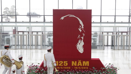 Musicians walk past a giant poster promoting the upcoming 125th birthday celebration of Vietnam's late revolutionary leader Ho Chi Minh in Hanoi