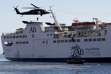 Members of the special forces abseil from a UH-60A Black Hawk helicopter as others use a rope ladder to board a ship during a boarding drill, part of the Eager Lion military exercise, in the coastal city of Aqaba
