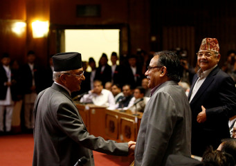 Nepal's Prime Minister Khadga Prasad Sharma Oli shakes hand with Chairman of the Unified Communist Party of Nepal (Maoist) Pushpa Kamal Dahal as he returns after announcing his resignation at the parliament in Kathmandu