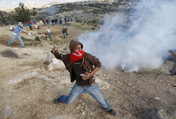 A Palestinian youth throws a stone towards Israeli soldiers during a weekly protest against the controversial Israeli barrier in Bilin near Ramallah