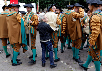 A woman adjusts the medieval costume of volunteer taking part in an annual Renaissance pageant, the Ommegang parade, in central Brussels