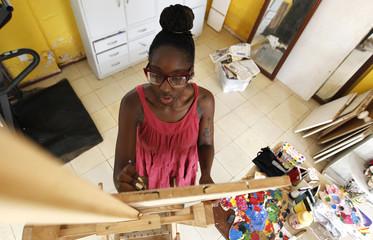Kenyan artist Wini Awuondo paints her creation on a wooden board inside her studio in Gigiri Nairobi