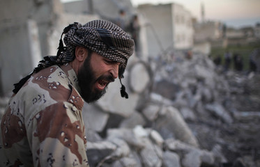 A Free Syrian Army fighter reacts after an air strike by a fighter jet loyal to Syrian President Bashar al-Assad in Azaz city