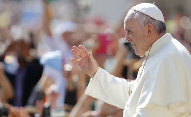 Pope Francis waves as he arrives to lead his weekly audience in St.Peter's square at the Vatican City