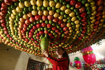 Member of the Samaritan sect decorates a traditional hut known as a sukkah with fruits and vegetables on Mount Gerizim, on the outskirts of the West Bank city of Nablus