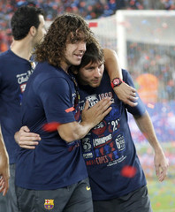 Barcelona's Lionel Messi and Carles Puyol embrace after their Spanish King's Cup celebration at Camp Nou in Barcelona