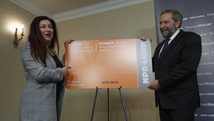 NDP leader Mulcair looks on as Independent MP Mourani prepares to sign a mock oversized NDP membership card during a news conference in Ottawa