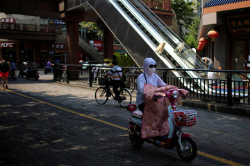 A woman, wearing a hood, mask and sunglasses to block the sun's rays, rides an electric bicycle in Hangzhou