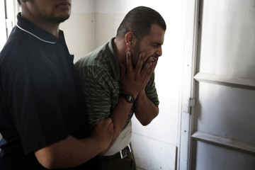 Father of two boys from the Shaibar family, whom medics said were killed along with a girl from same extended family by Israeli air strike after end of a five-hour humanitarian ceasefire, grieves at morgue in Gaza City