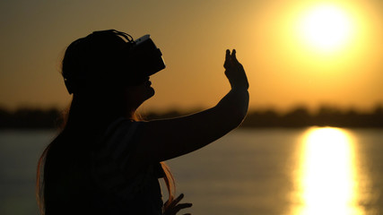 Woman in virtual reality glasses on the sunset background.