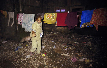 Javed Sheikh holds a rat by the tail as he tries to kill it by hitting on the ground at a residential complex in Mumbai
