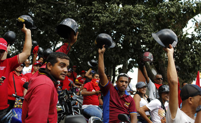 Motorcyclists raise their helmets in support of Venezuela's late President Hugo Chavez during a rally around Caracas