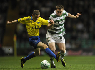 Dunfermline Athletic's Paul Burns is challenged by Celtic's James Forrest during their Scottish Premier League soccer match at Parkhead Stadium, Glasgow, Scotland