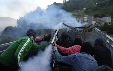 Coal miners fire a rocket during a clash with Spanish national riot police in the surroundings of the El Soton coal mine in El Entrego
