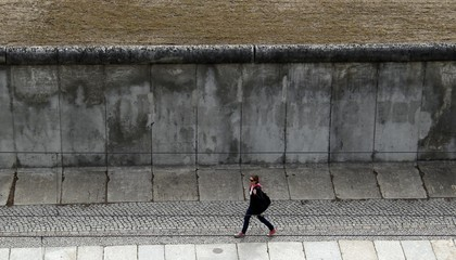 A woman walks next to the Berlin Wall memorial at the Bernauer Strasse in Berlin