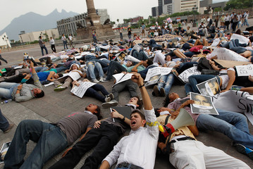 Students lie on the floor in front of the Government palace after a silent march against drug related violence in downtown Monterrey