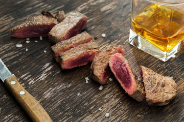 Sliced grilled beef steak on wooden table with whiskey
