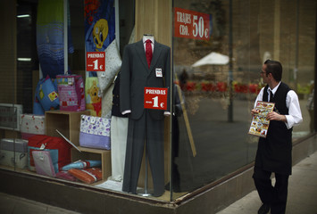 A waiter looks at a shop window in the Andalusian capital of Seville