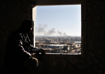 A Free Syria Army fighter watches from his position as smoke during a fight with forces loyal to President Bashar al Assad at the front line in Aleppo