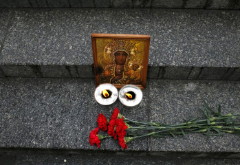 An icon, candles and flowers are seen during a rally in memory of people who died during shelling in the southern Ukrainian city of Mariupol on Saturday, in Kiev