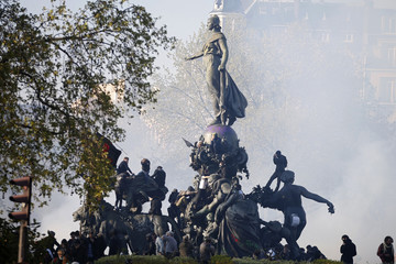 Youths gather on a statue at the Place de la Nation which fills with tear gas as French CRS riot police advance at the end of a protest against the French labour law proposal during the May Day labour union march in Paris