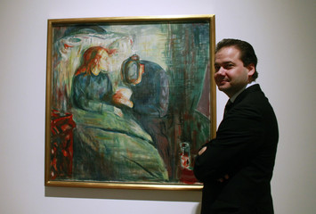 """Hollein, director of the Schirn Kunsthalle Frankfurt gallery poses next to the painting """"The Sick Child"""", 1925 by Norwegian artist Edvard Munch presented at an exhibition in Frankfurt"""