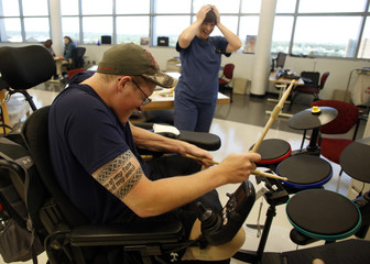 Sgt. Matt Krumwiede of the U.S. Army plays a drumming computer game during occupational therapy at Brooke Army Medical Center in San Antonio